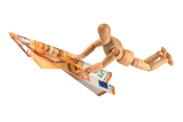 wooden mannequin surfing on Euro money note stock photo