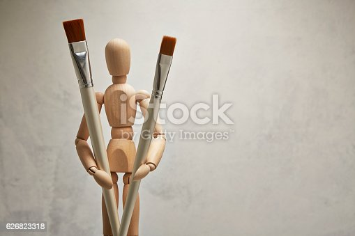 istock Wooden mannequin with paintbrush 626823318