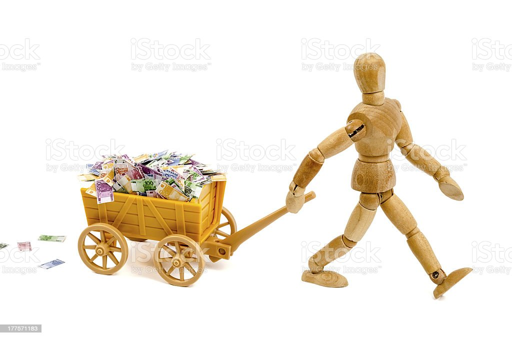 Wooden mannequin with trolley full of euro notes royalty-free stock photo