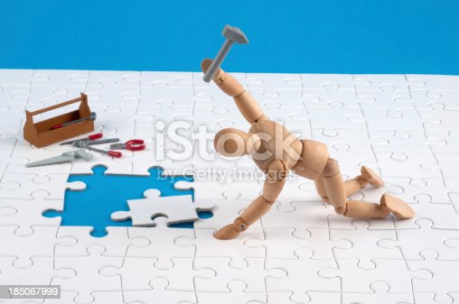 it must in! wooden mannequin working hard at a jigsaw. Is this the right piece? Never mind!