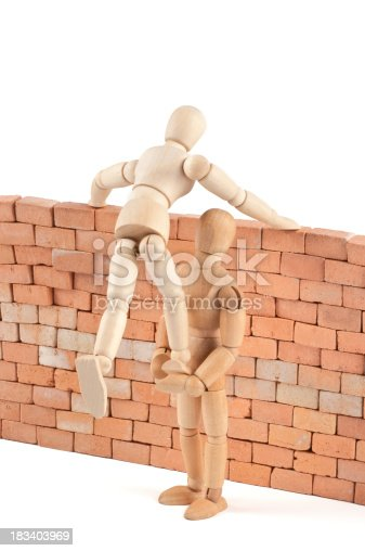 istock wooden mannequins gives a leg up over the wall 183403969