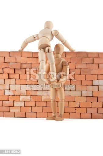 istock wooden mannequins gives a leg up over the wall 183418080