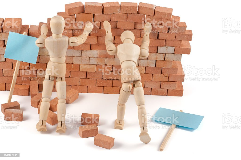 wooden mannequins pushing the wall stock photo