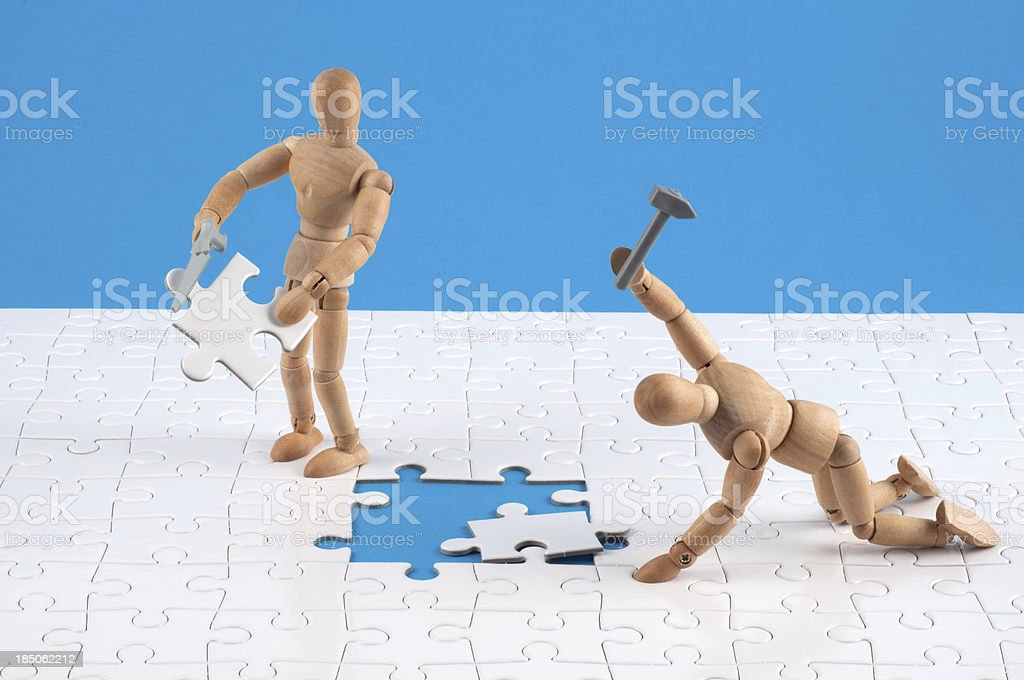 wooden mannequins working hard at a jigsaw. royalty-free stock photo