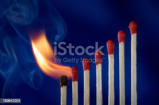 istock Wooden matches lined up like dominoes steps, in flames 163642024
