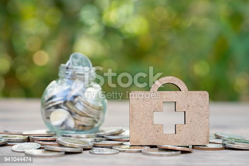 istock Wooden medical bag on coins stack with jar of coins as backdrop. Concept of money saving, financial, life insurance, retirement, investment. 941044474