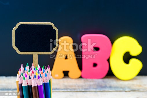 istock Wooden mini blackboard label and colouring pencils over chalkboard background 613346570