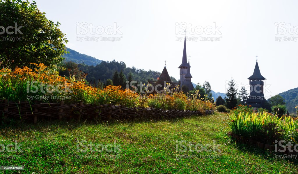 Wooden monastery and flowers at Barsana, Maramures, Romania stock photo