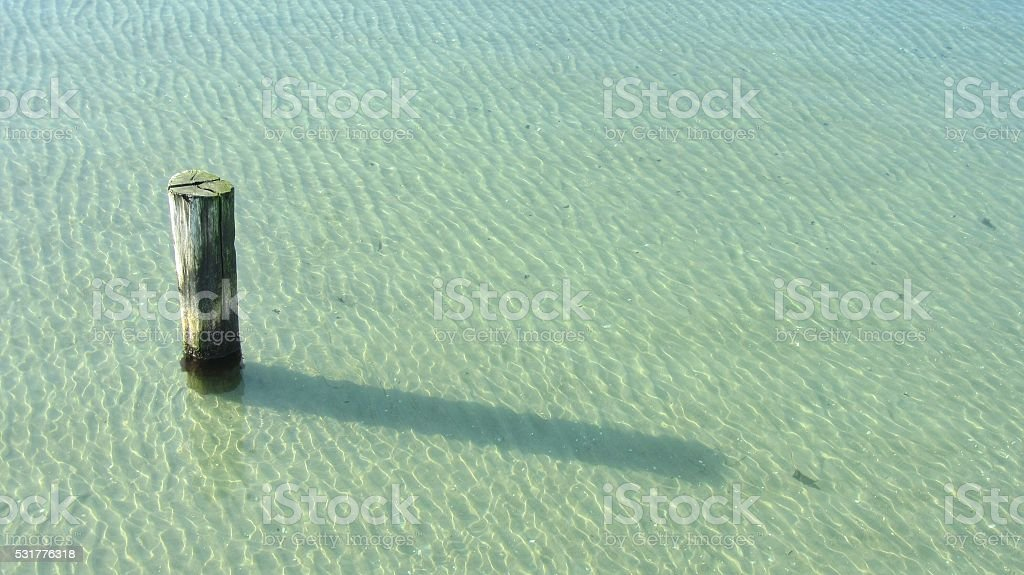 Wooden mooring pole in clear shallow water stock photo