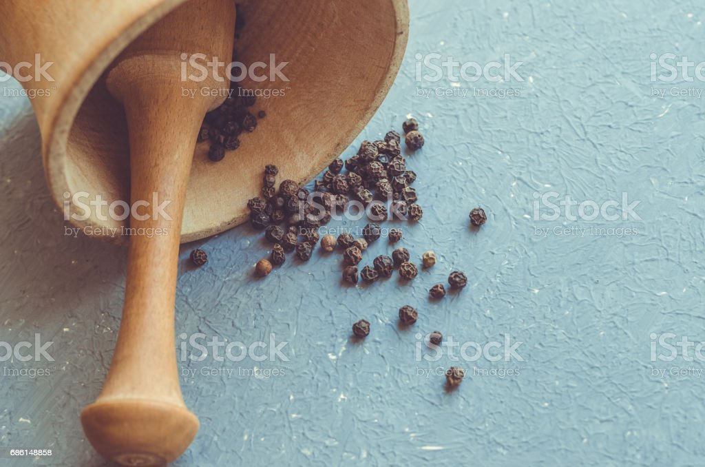 Wooden mortar and pestle with black pepper on grey background stock photo