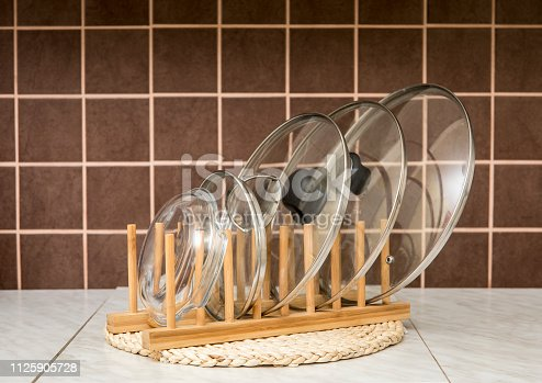 Wooden natural color rack for holding pot/pan lids in kitchen, brown tiles on the background. Kitchen organizer interior element tool concept.