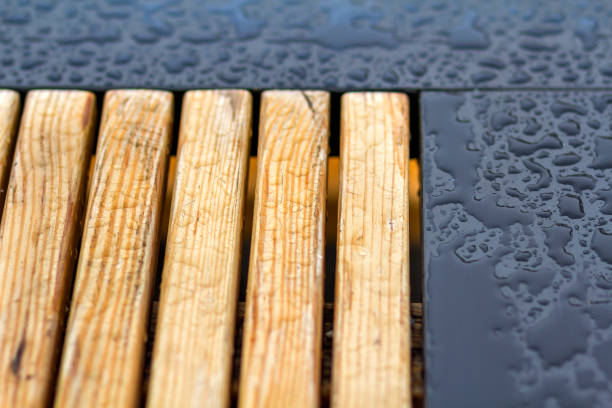 Wooden natural planks, polished boards, garden park bench with transparent big clear rain water drops on blue gray wet background. Empty place for recreation in bad weather. stock photo