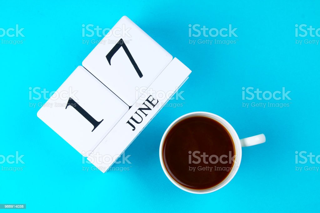 A wooden notebook with a date on June 17 and a coffee mug on a blue pastel background. Father's Day. stock photo