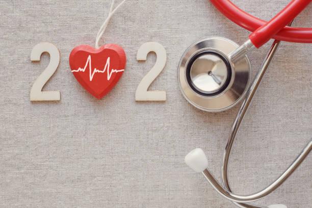 2020 Holznummer mit rotem Stethoskop. Frohes neues Jahr für Herzgesundheit und medizinisches Konzept, Lebensversicherungsgeschäft – Foto