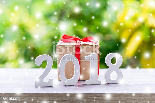 istock Wooden numbers forming the number 2018, For the new year with snow and gift box on wood table background. 860153070