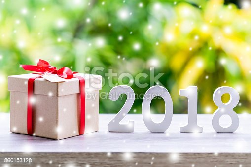 istock Wooden numbers forming the number 2018, For the new year with snow and gift box on wood table background. 860153128
