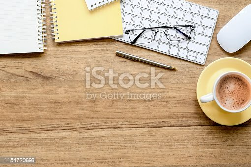Wooden office desk with cup of coffee, white keyboard, mouse, pen,glasses and yellow notebook. Top view. Tabletop. Copy space.