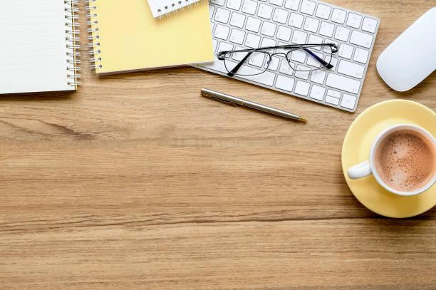Escritorio de oficina de madera con taza de café, teclado blanco y suministros. - foto de stock