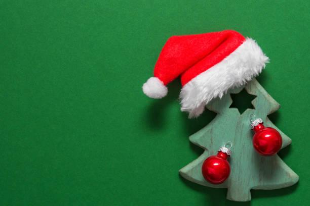 Hölzerne Ornament Weihnachtsbaum mit roten Kugeln Weihnachtsmann Hut auf grünem Hintergrund verziert – Foto