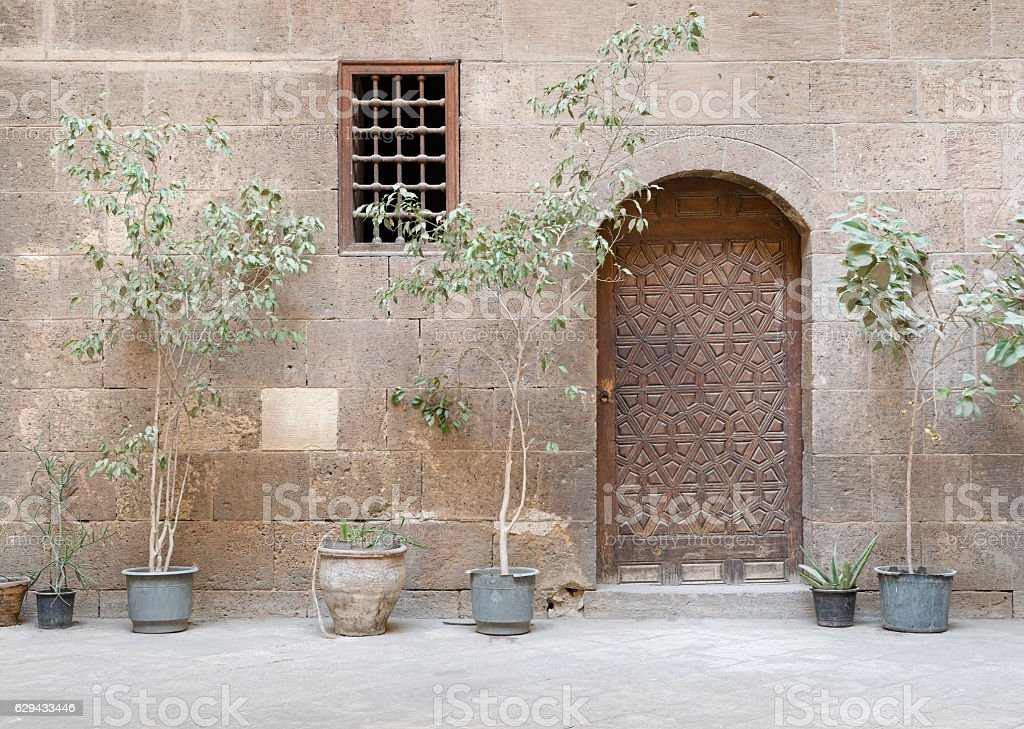 Wooden ornate door and small window with wooden grid, Cairo stock photo
