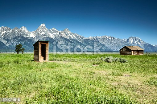 Wooden outhouse and barn are part of a series of structures in a historic settlement called Mormon Row. This settlement is near the base of the Grand Tetons.