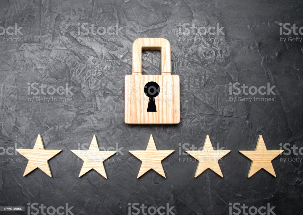 A wooden padlock and five stars. Security, security of users and business. Internet security, antivirus, data protection. Alarms of home, car and business. The concept of property protection. stock photo