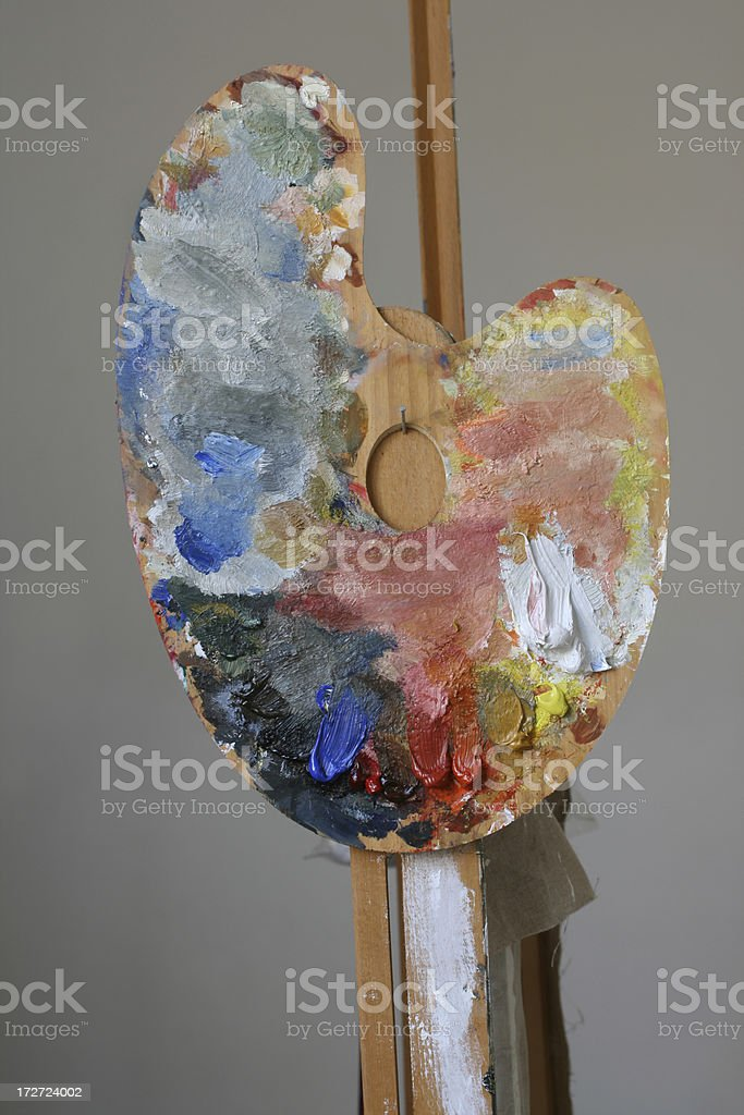Wooden palette with oil paint hanging on the easel royalty-free stock photo