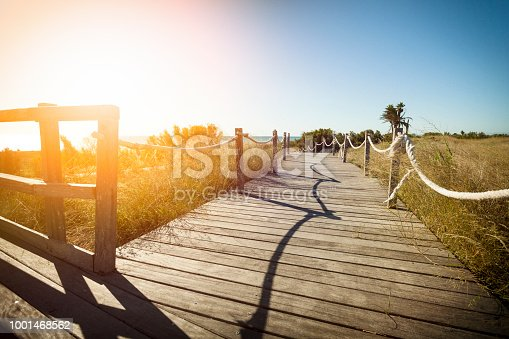 Horizontal view of a wooden path to the beach on the dunes at sunset. Copy space available for text and/or logo. DSRL outdoors photo taken with Canon EOS 5D Mk II and Canon EF 17-40mm f/4L IS USM Wide Angle Zoom Lens