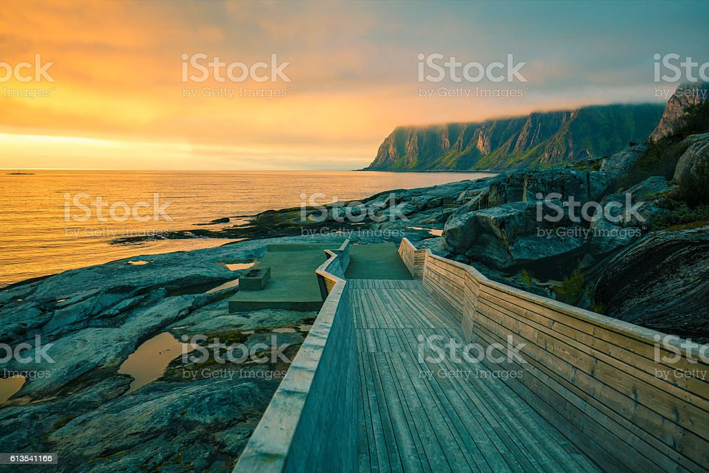 Wooden pathway on the rocky beach stock photo