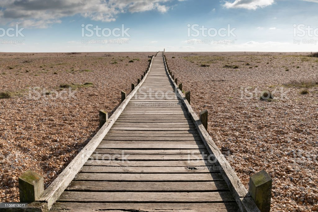Wooden pathway on the stone beach stock photo