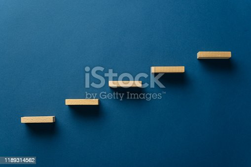 Wooden pegs place over navy blue background in a stairway like structure in a conceptual image. With copy space.