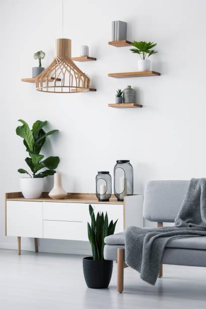 holzanhänger licht, regale einfach auf eine weiße wand und eine anlage auf einem skandinavischen sideboard in einem monochromen wohnzimmer interieur - sideboard skandinavisch stock-fotos und bilder