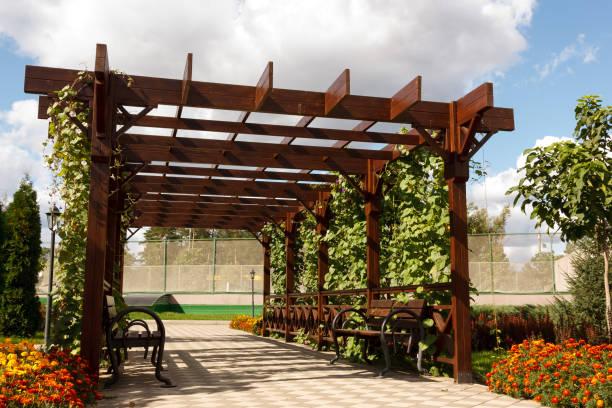 Holzpergollas aus Naturholz mit bequemen Bänken in einem modernen Landdorf an einem sonnigen Sommertag. Der gepflasterte Weg wird an Blumenbeeten, Ziersträuchern und Bäumen vorbeigelegt. Russland – Foto