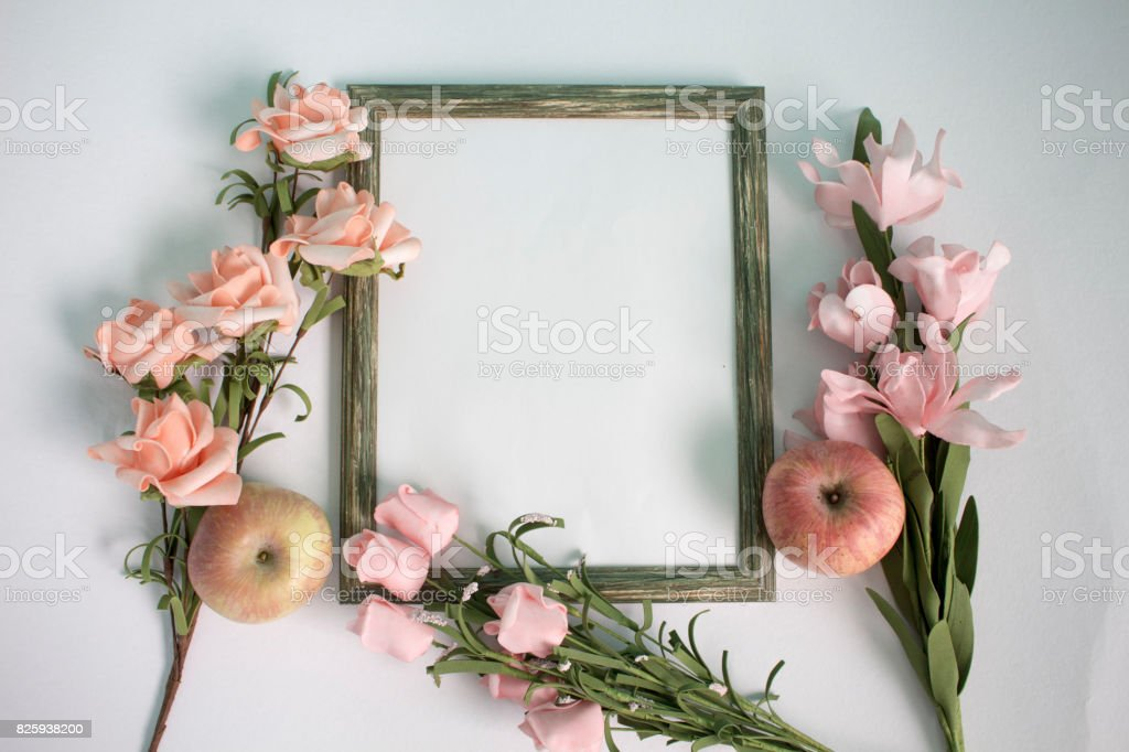 Wooden photo frame, apple and pink roses on watercolor paper. Flat lay table with gentle floral ornament. stock photo