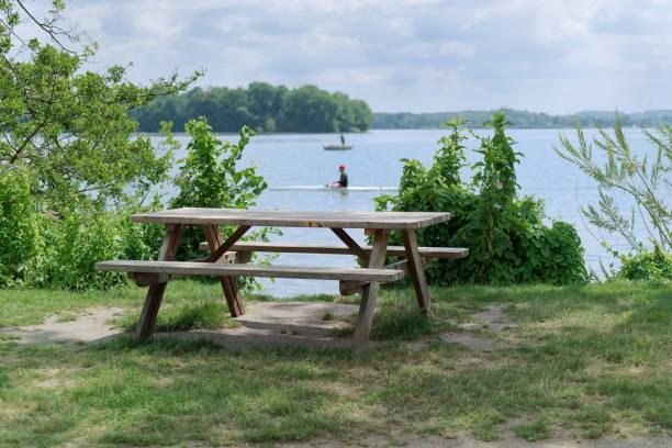 wooden picnic table at the lake coast stock photo