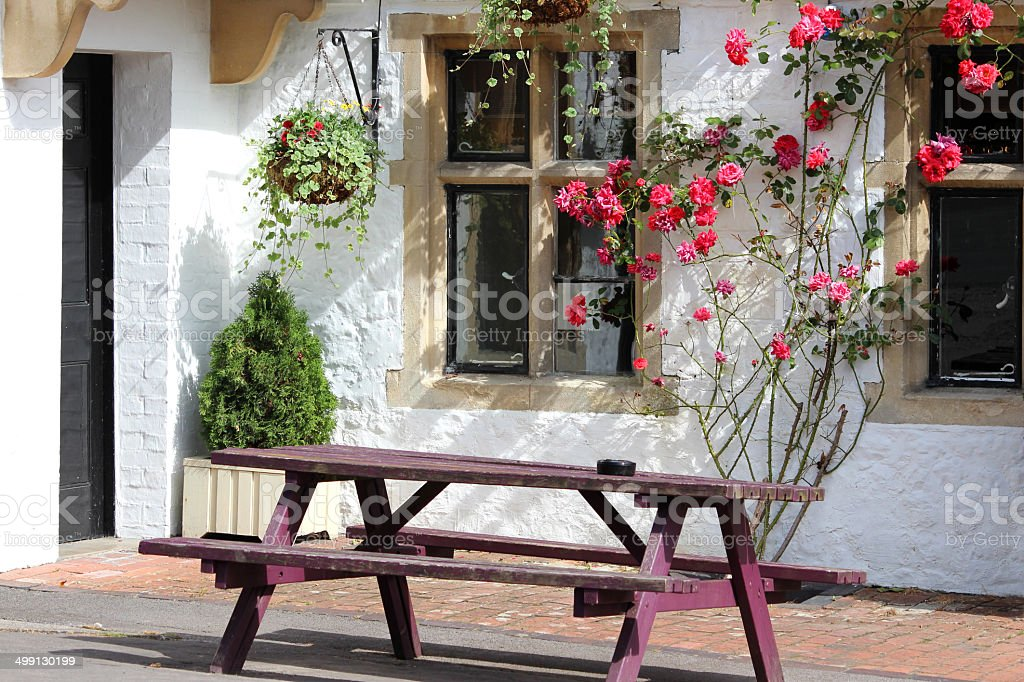 Wooden picnic table outside house with pink climbing rose flowers stock photo