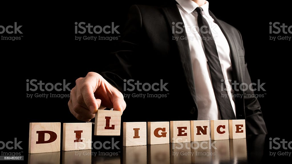 Wooden Pieces with Diligence Text on Black Background stock photo
