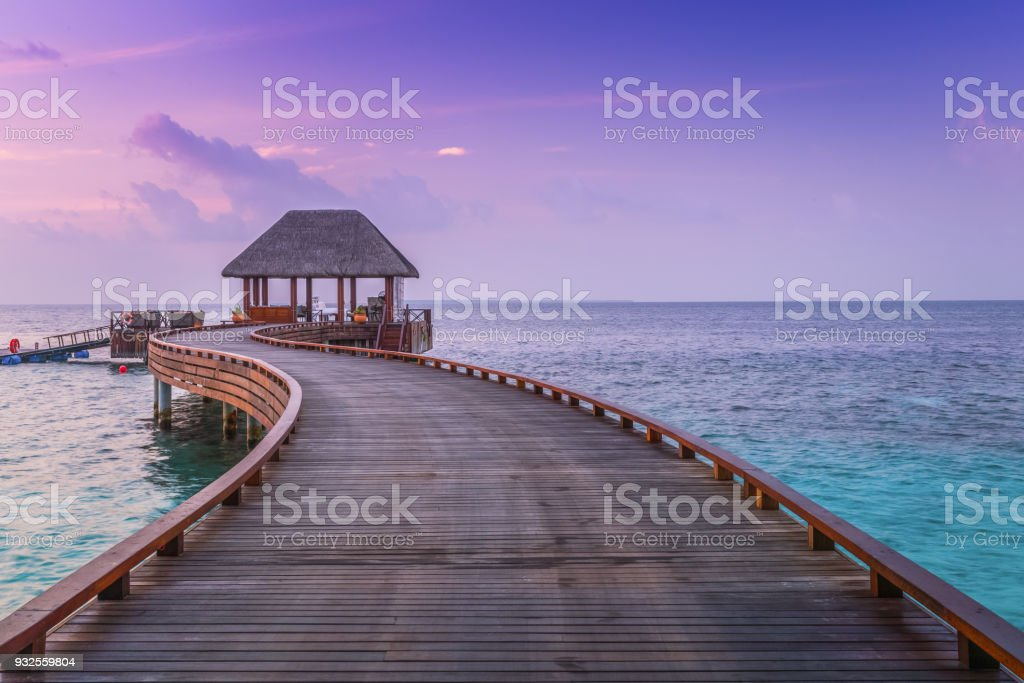 Wooden pier and blue sea at Maldives in sunset stock photo