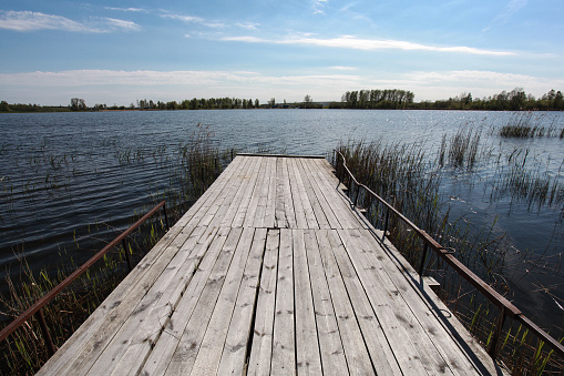 Wooden pier and grass on lake shore on sunny summer day with beautiful clouds on blue sky