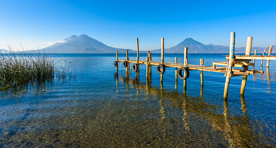 istock Wooden pier at Lake Atitlan on the shore at Panajachel, Guatemala.  With beautiful landscape scenery of volcanoes Toliman, Atitlan and San Pedro in the background. 896430454
