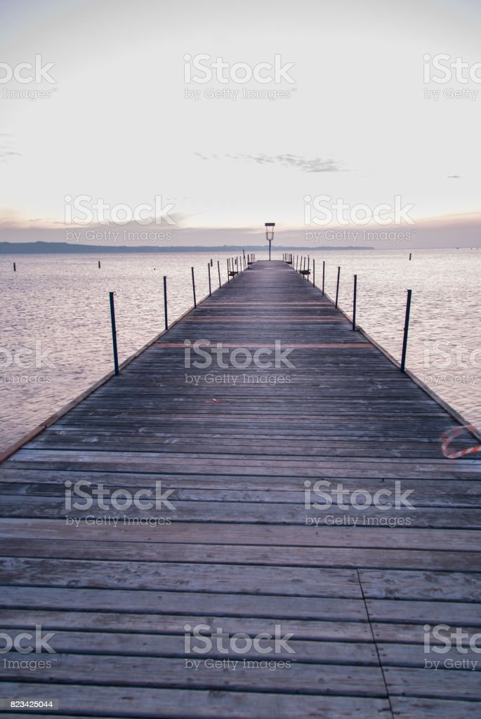 Wooden pier entering into the sea with colorful morning sky stock photo