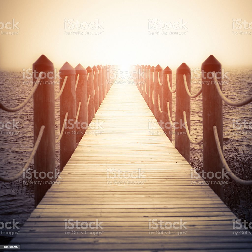 Wooden pier fading into light at horizon stock photo