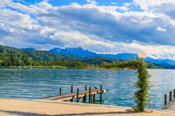 holzsteg zum festmachen von booten auf see wörthersee an schönen sommertag, österreich - wörthersee stock-fotos und bilder