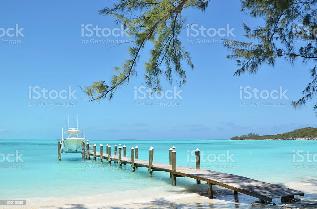 Wooden pier in the Bahamas with boat in background stock photo