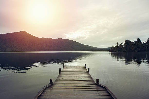 wooden pier lying on lake kaniere - pier stock photos and pictures