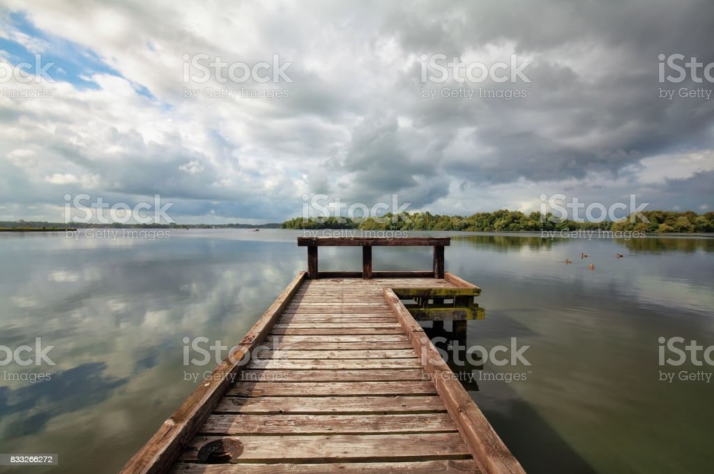 wooden pier on big lake during sunny summer day stock photo