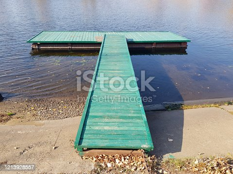 Wooden pier on the river. Autumn weather.