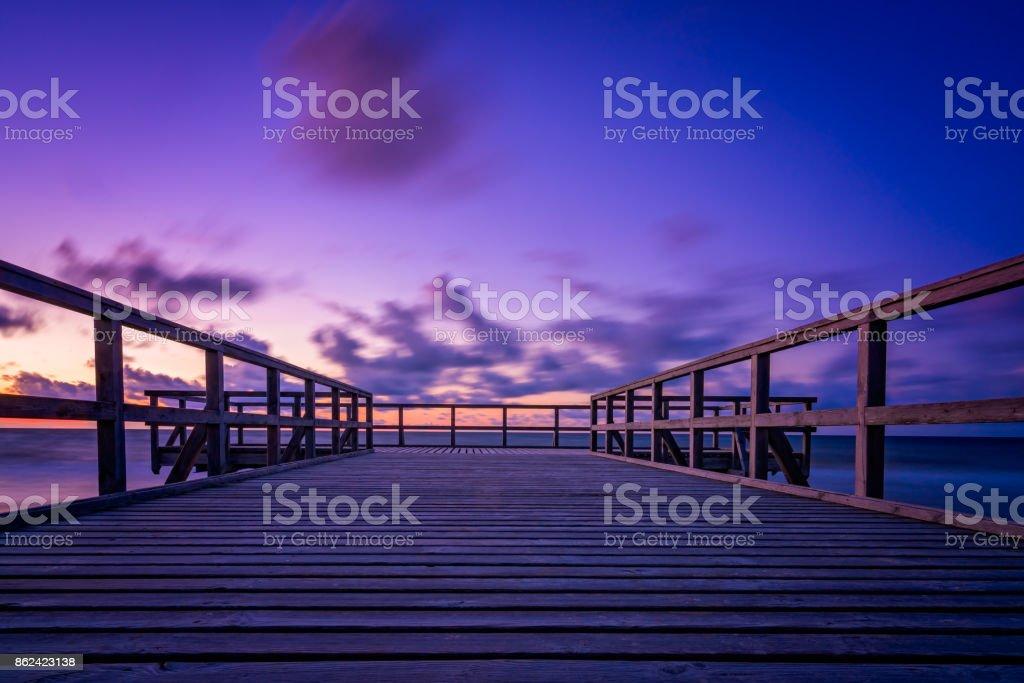Wooden pier on the sea beach at sunset stock photo