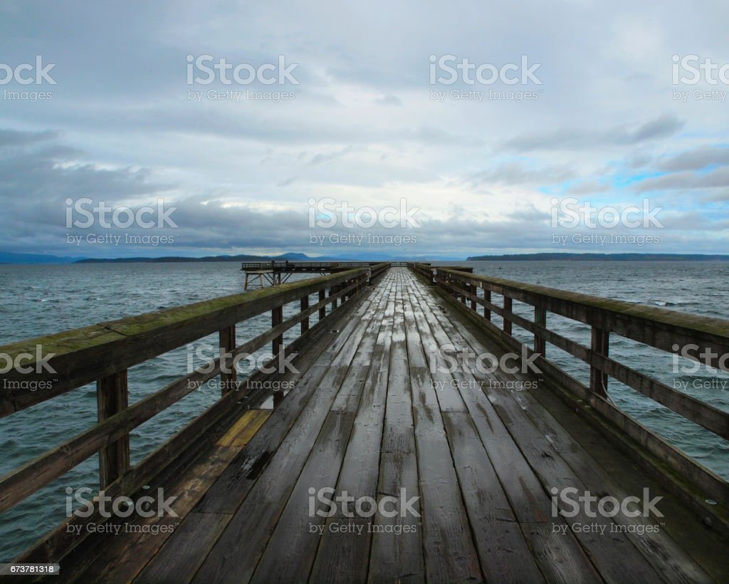 Wooden pier under stormy clouds after the rain royalty-free stock photo