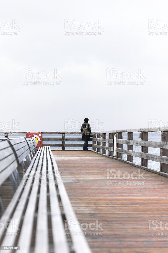Wooden pier with a lonely woman stock photo